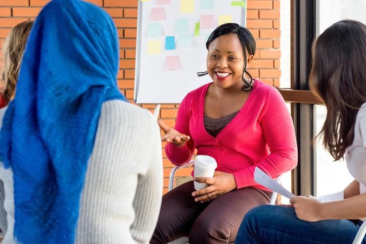 black woman talking to a diverse group