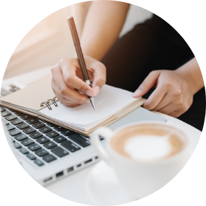 Person writing in a notebook by a laptop and coffee